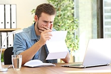 young man at office desk reading a letter with concern